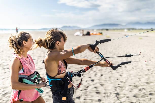 junge frau und ihr lehrer bereiten sich auf das kitesurfen am strand vor. - kitesurfen lernen stock-fotos und bilder