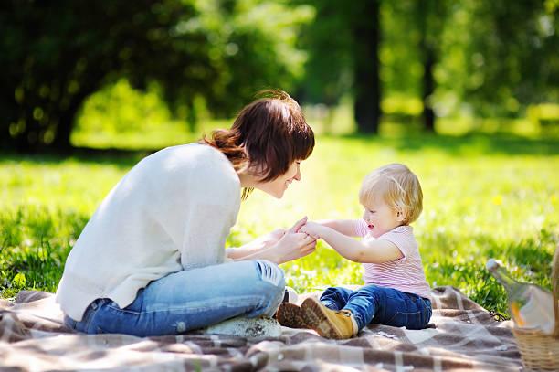 junge frau und ihrem kleinen sohn im sonnigen park - kinder picknick spiele stock-fotos und bilder