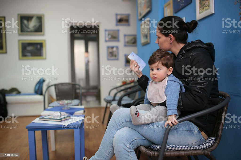 Young woman and her son at the doctor stock photo