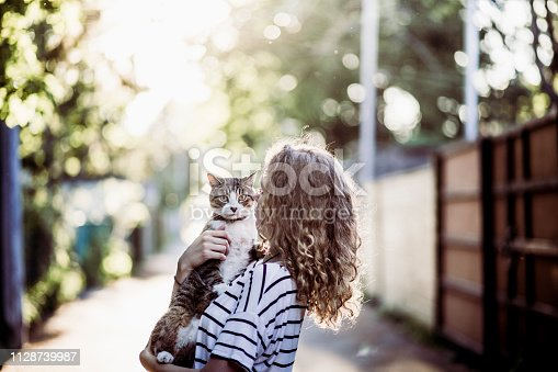 domestic cat, one young woman only, Montreal, alley, holding