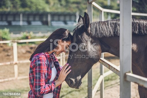 a young woman on a horse farm spends time with her horses
