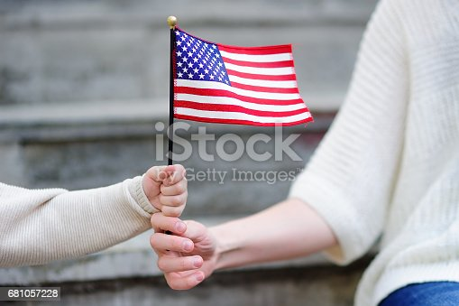 istock Young woman and little child holding american flag 681057228