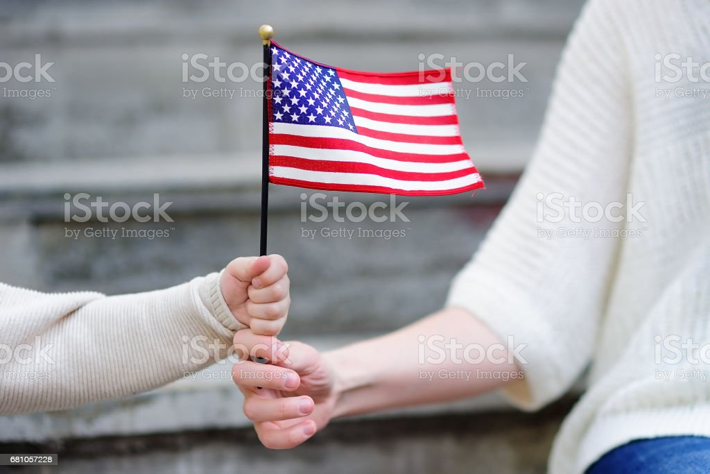 Young woman and little child holding american flag stock photo