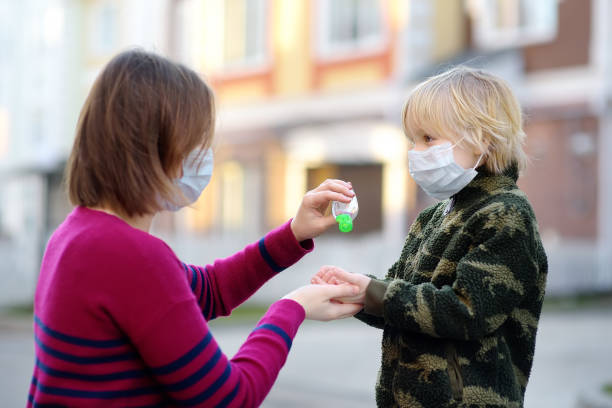 Young woman and little child wearing a protective mask makes disinfection of hands with sanitizer in airport, supermarket or other public place. Safety during COVID-19 outbreak. stock photo