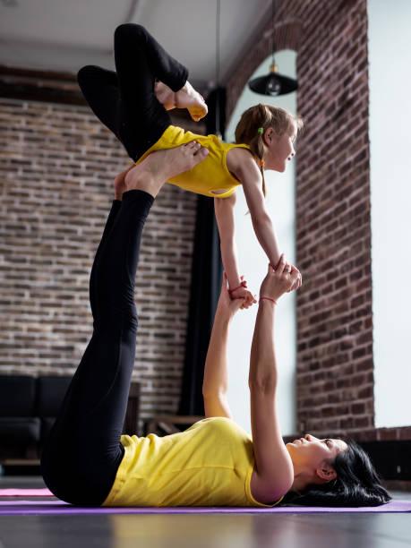 Jeune femme et petite fille faire du yoga partenaire flying pose exercer ensemble - Photo