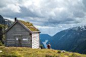 Woman by Kiellandbu in front of Hardanger fjord in Norway.