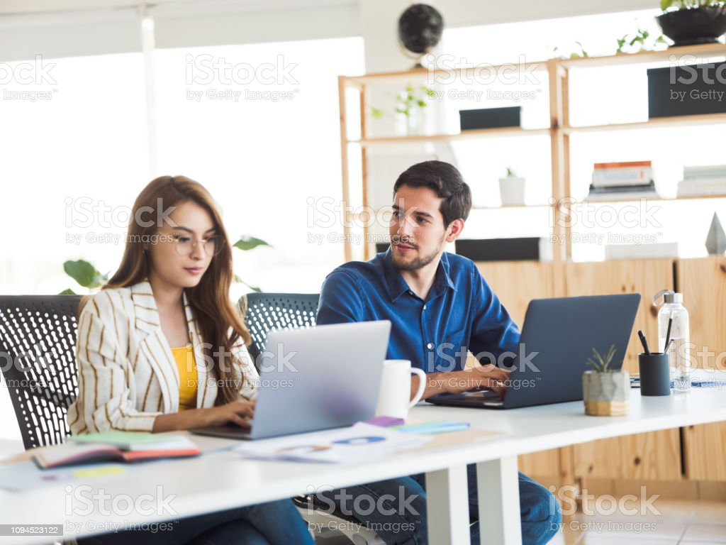 Young woman and man at the office working stock photo