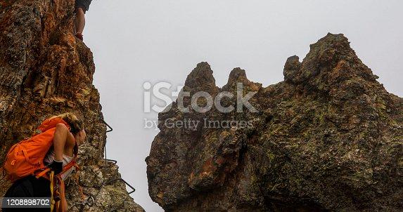istock Young woman and man climb via ferrata ladder up rocky ridge in the mist 1208898702