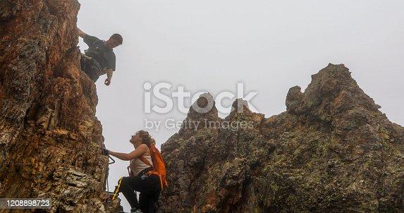 istock Young woman and man climb via ferrata ladder up rocky ridge in the mist 1208898723