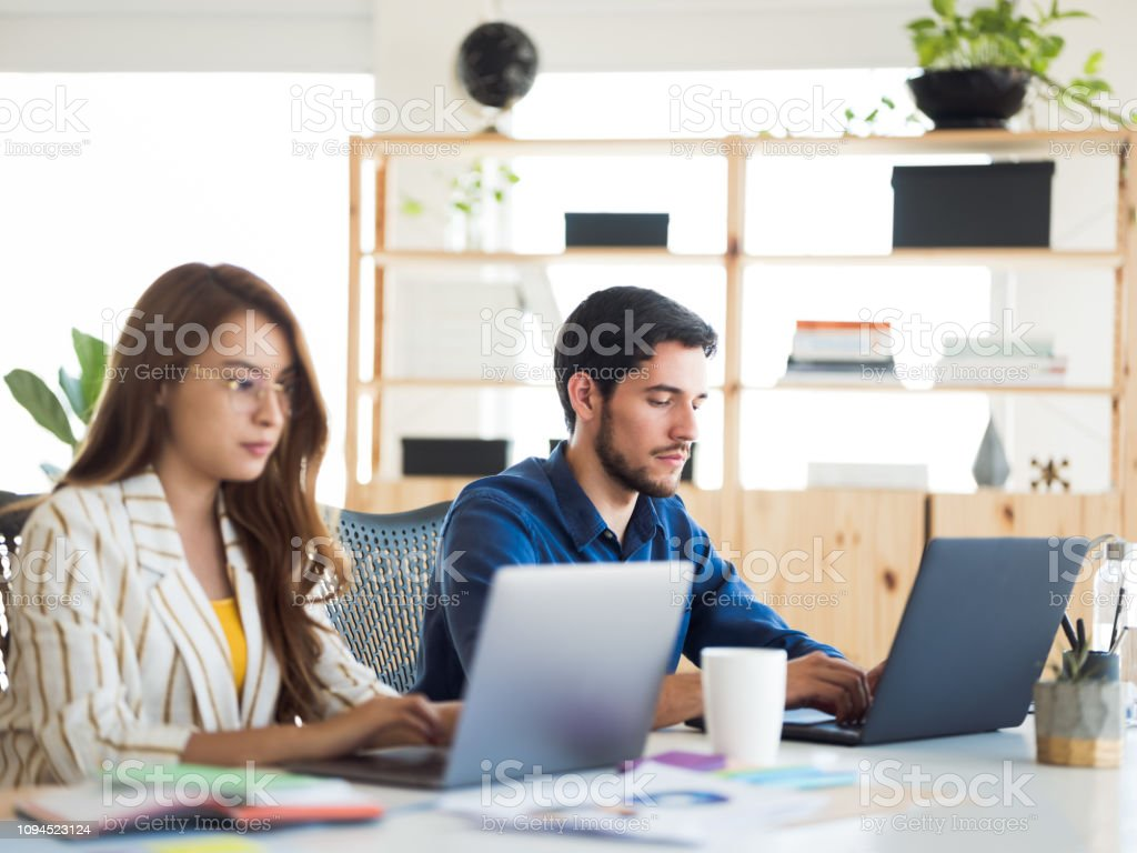 Young woman and man concentrated working stock photo