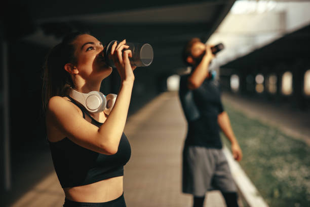 Young woman and man drinking protein shake after workout stock photo