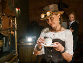istock Young woman and man in steampunk stile make a coffee 169998228