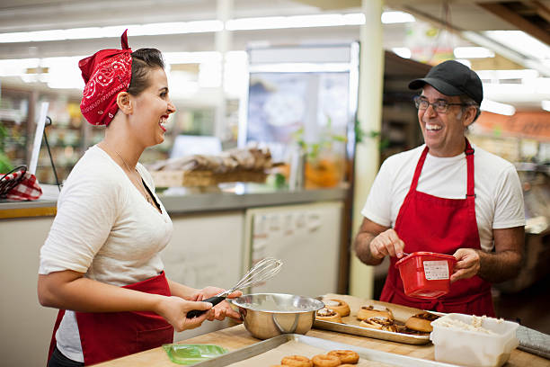 Young woman and man laughing in commercial kitchen stock photo