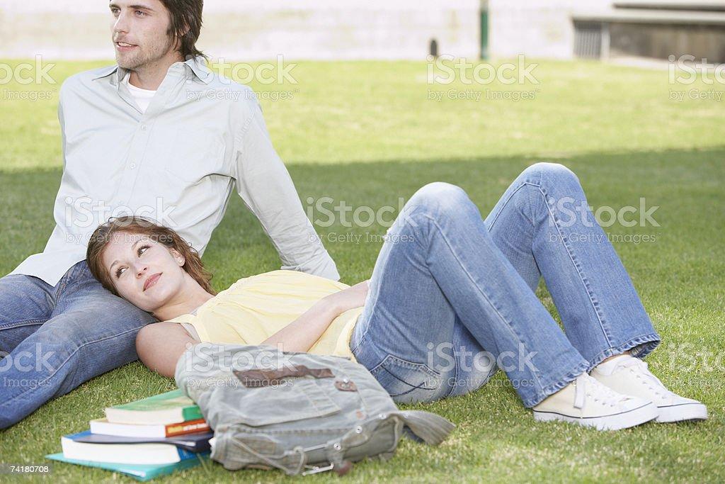 Jovem mulher e o homem que estabelece na grama com Livros foto de stock royalty-free