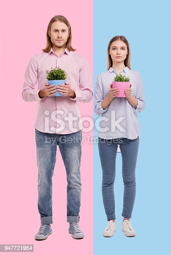 istock Young woman and man posing with flower pots 947721954