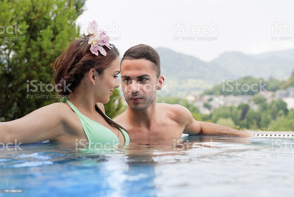young woman and man relaxing in resort swimming pool royalty-free stock photo