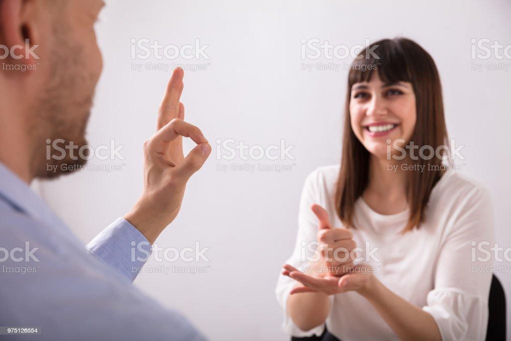Junge Frau und Mann im Gespräch mit Gebärdensprache – Foto