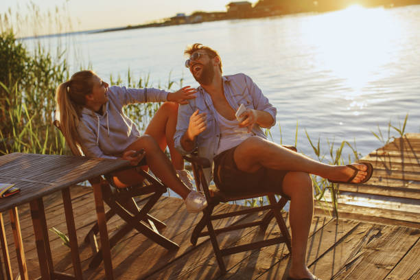 Junge Frau und Mann mit Smartphone und Lachen am Fluss – Foto
