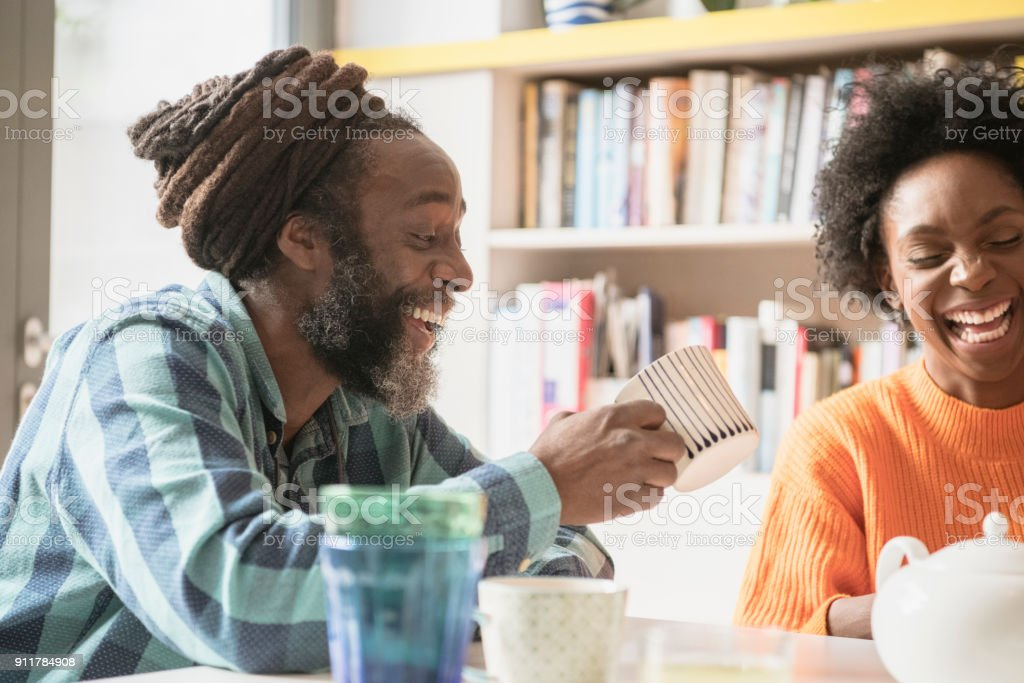 Young woman and mature man with dreadlocks in kitchen laughing stock photo