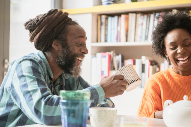 Young woman and mature man with dreadlocks in kitchen laughing African man in his 50s with mug of tea sitting at table with grown up daughter and smiling afro caribbean ethnicity stock pictures, royalty-free photos & images