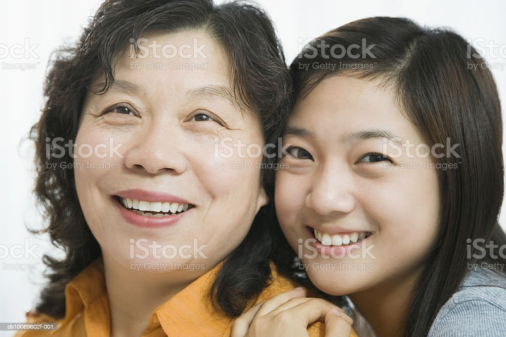 Young woman and mature woman smiling, close-up royalty free stockfoto