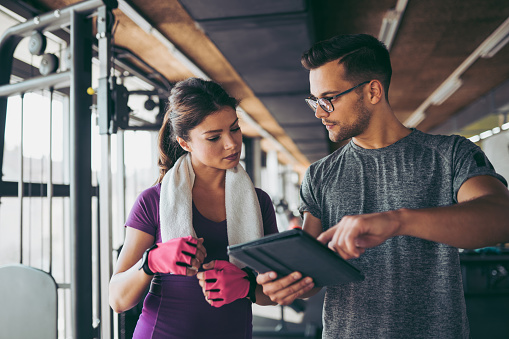 860045834 istock photo Young woman and personal trainer making exercise plan in gym 1058420056