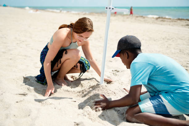 Young woman and preteen boy placing an umbrella on the beach. stock photo