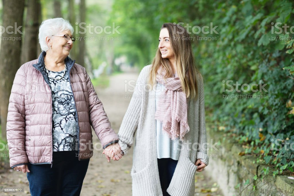 young woman and senior adult walking together holding hands stock photo