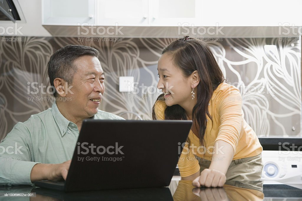 Young woman and senior man using laptop, smiling royalty-free stock photo