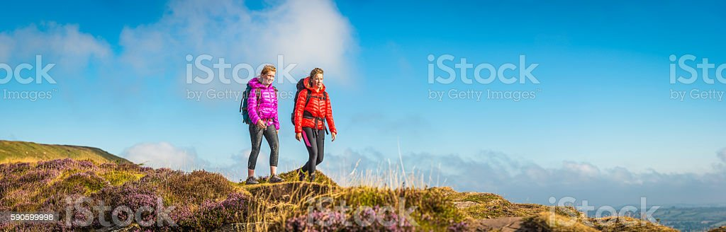 Young woman and teenage hiker walking picturesque summer mountain panorama stock photo