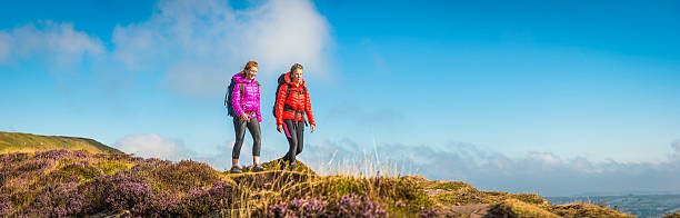 Young woman and teenage hiker walking picturesque summer mountain panorama Young hikers walking along mountain ridge, Brecon Beacons National Park, Wales, UK. brecon beacons stock pictures, royalty-free photos & images