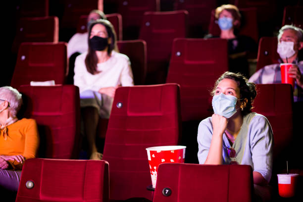 Young woman and the other spectators wearing protective face masks at the cinema Audience at the cinema wearing protective face masks and sitting on a distance while watching the movie. film industry stock pictures, royalty-free photos & images