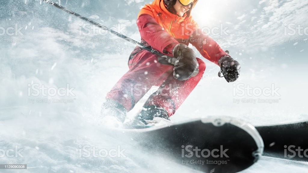 Young beautiful athlete woman doing winter sport - she is skiing...