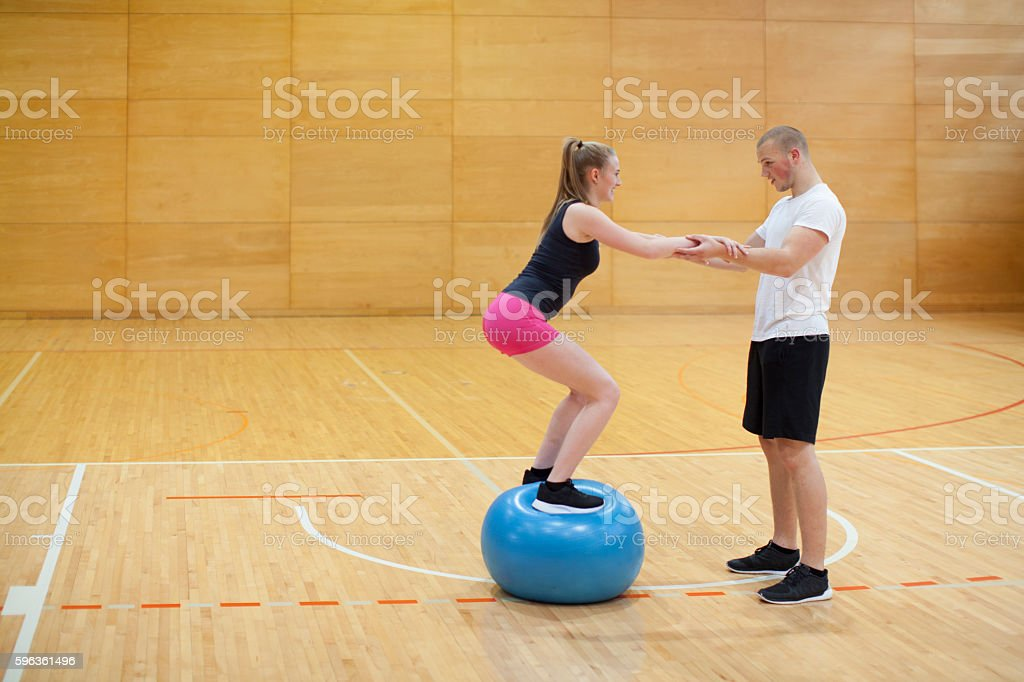 Young Woman and Young Man Practice Fitness in Gym royalty-free stock photo