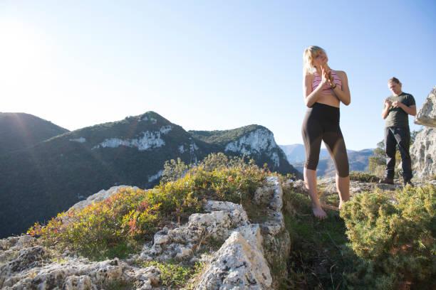 junge frau und junger mann auf felsvorsprung in bergen - spitzen crop tops stock-fotos und bilder