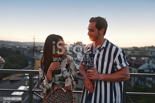 young woman and young men talking with beer on the top of the roof