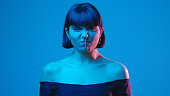 istock Young woman angry yell isolated on blue neon copyspace 1303517433