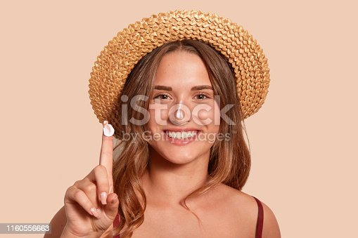 istock Young woman applaying sunblock on her face, and showinig her finger with sunscreen, model posing isolated over beige background, standing against studio wall with topothy smile, dressed swimming suit. 1160556663