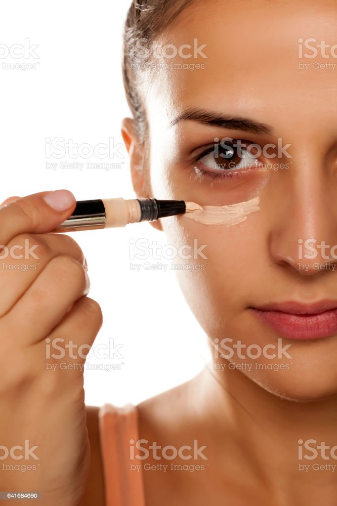 young woman applied concealer on her eye circles stock photo
