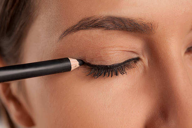 young woman applied eyeliner stock photo