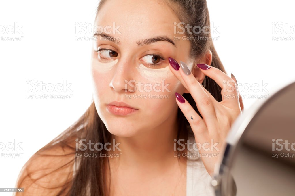 A young woman applies a concealer under the eyes stock photo