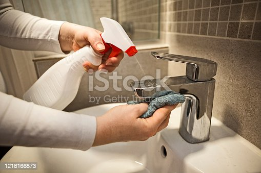 Woman applies an alcohol-based antiseptic spray to a water tap