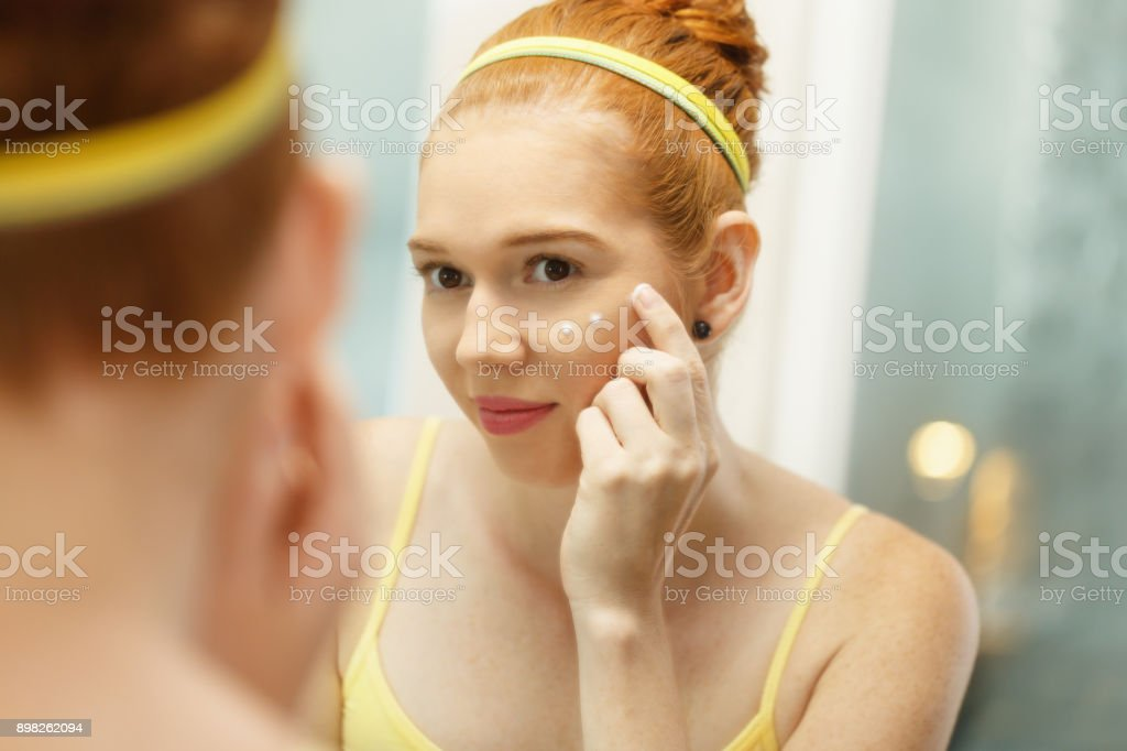 Young Woman Applies Anti-Aging Cream Looking At Mirror stock photo