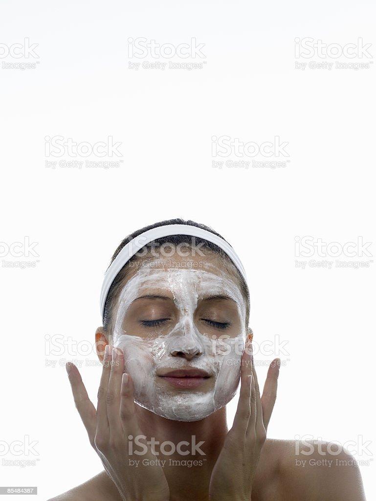 Young woman applies cleanser to face photo libre de droits