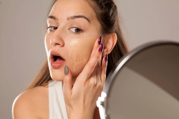 young woman applying a liquid foundation on her face with her fingers stock photo