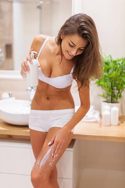 junge frau anwenden körperlotion - feminine badezimmer stock-fotos und bilder