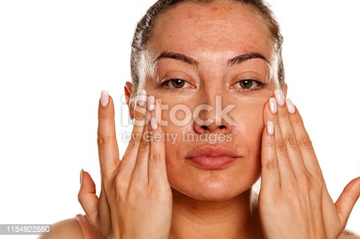 Young woman applying concealer under her eyes with her fingers on white background