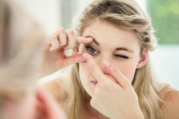 jovem mulher aplicando lente de contato - inserindo - fotografias e filmes do acervo