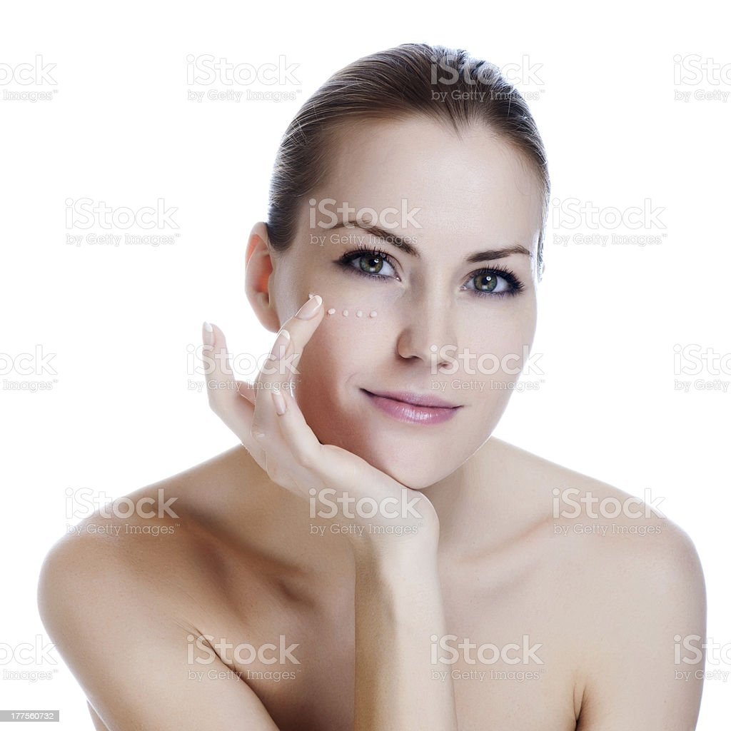 Young woman applying cosmetic cream under her eye stock photo
