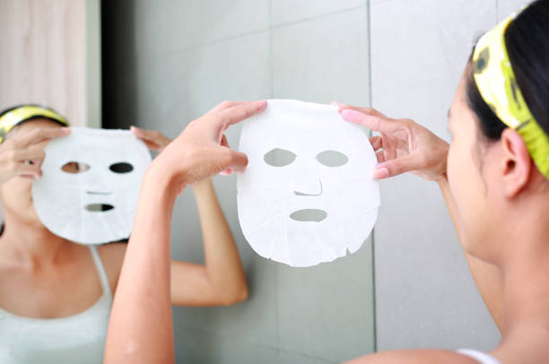 Young woman applying cosmetic facial mask in the bathroom. stock photo